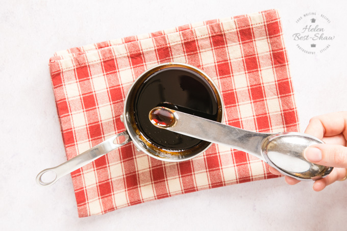 A top down view of a small saucepan containing a balsamic vinegar and pomegranate molasses reduction. A measuring spoon holds a small quantity of the sauce to indicate the consistency.