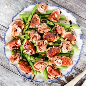 Fig and green bean sald with Parma ham. The salad, on a white plate with a blue rim, is dressed and garnished with toasted pine nuts.