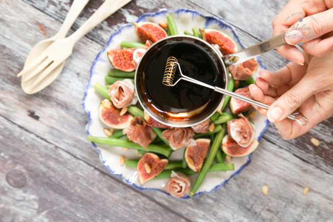Dressing fig and green bean salad with Parma ham. A small whisk is being used to transfer the dressing from a small saucepan to the salad.