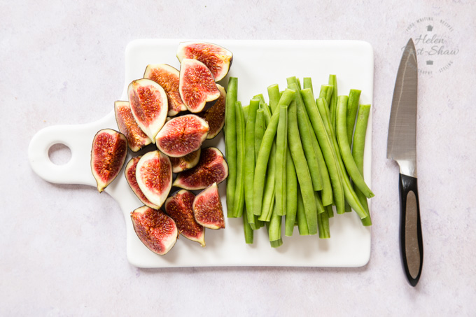 Prepared green beans and figs on a square white porcelain board. The figs have been quartered, and the beans have had their ends trimmed off.