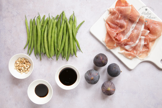The ingredients for fig and green bean salad with Parma ham. Slices of Parma ham on a white, glazed board. A handful of green beans lying on the mottled grey worktop, along with four figs. Three small bows containing pine nuts, balsamic vinegar and pomogranate molasses.