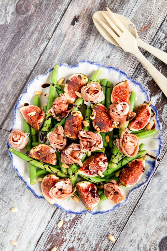 A top down view of a salad made wtih green beans, figs and garnished with parma ham roses