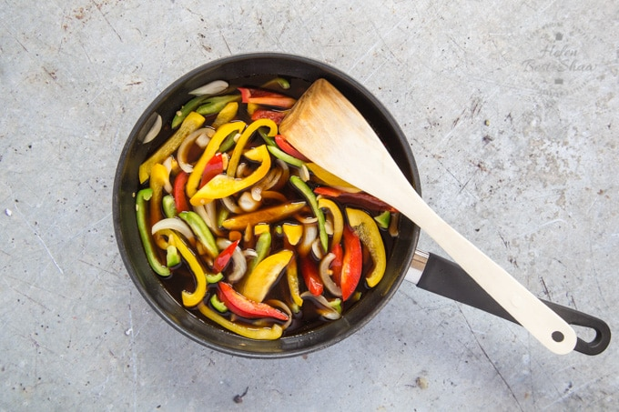 A frying pan full of sliced red, yellow and green peppers, to which liquid sweet and sour sauce has been added. The frying pan sits on a rustic grey stone worksurface. A wooden spatula lies in the pan.