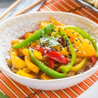 A close up on a bowl of peppers, coated with easy sweet and sour sauce and garnished with black and white sesame seeds. A dish of rice is out of focus in the background, along with a small bowl of more sweet and sour sauce. The main bowl is placed on a mat woven from wooden slats, alternating wider orange and thinner natural wood colours.