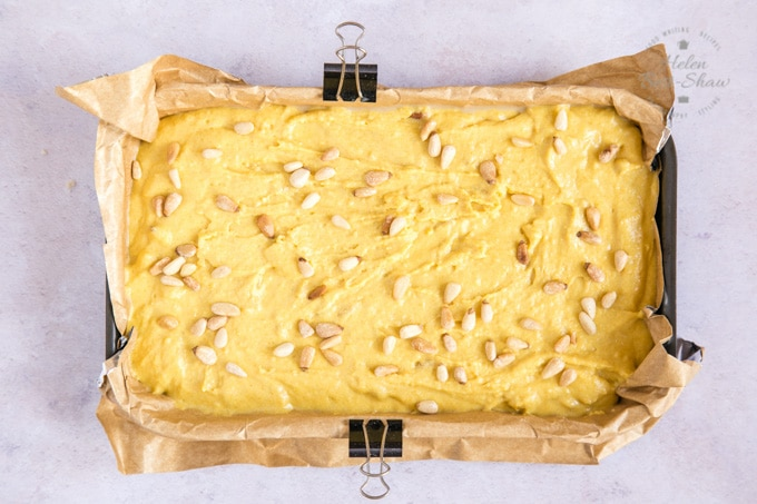 A top down photo of turmeric cake ready to be baked. The cake batter has been poured into a parchment lined cake tin. The parchment has been clipped to the tin with small bulldog clips