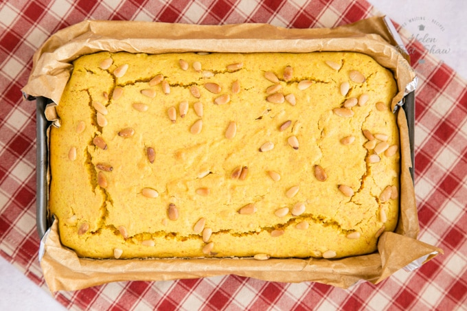 A top down view of baked turmeric cake just out of the oven. The cake has been baked in a rectangular, parchment lined cake tin which is sitting on a cream and red checked cloth.