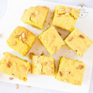 A top down view of eight square slices of yellow sfoof turmeric cake on a white square porcelain board.