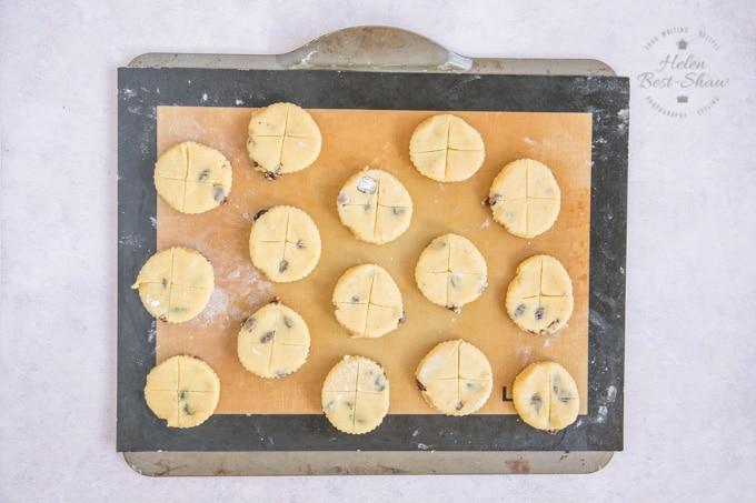 A picture taken from above of a baking tray, covered with a silicone baking mat, with fifteen soul cake biscuits arranged on it, ready to be baked.