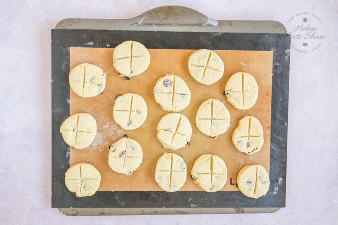A picture taken from above of a baking tray, covered with a silicone baking mat, with fifteen freshly baked soul cake biscuits arranged on it