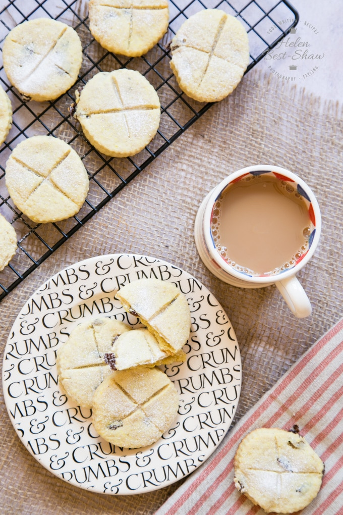 A shot from above of soul cakes being enjoyed with a mug of tea. A sideplate sits on a hessian cloth next to a mug of tea. Three soul cakes, with crosses cut into the top, sit on the sideplate, one broken in two. Another cake rests on a beige and red striped cloth at the bottom of the picture, and more are seen on a cooling rack at the top.