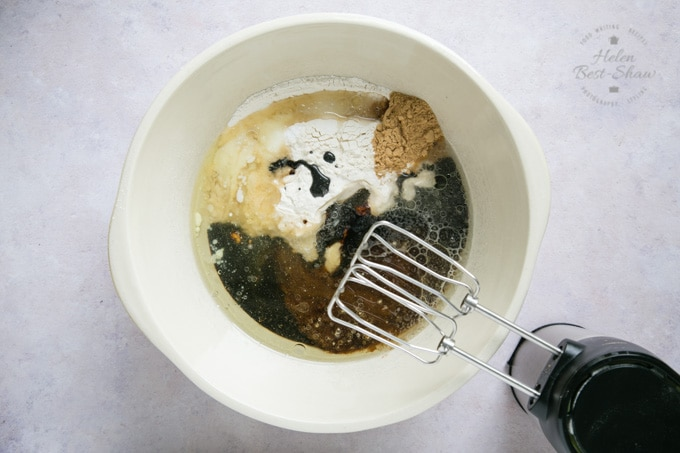 A top down shot of the ingredients for vegan ginger cake in a cream mixing bowl. An electric hand mixer is next to the bowl, ready to mix the ingredients.