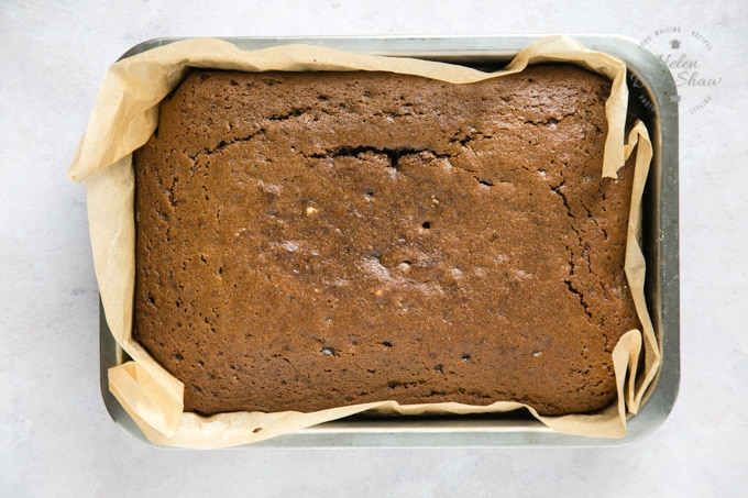 A top down picture of a baked easy vegan ginger cake in greaseproof paper in a rectangular cake tin. There are some cracks in the top of the cake.