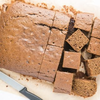 A picture from above of a baked rich brown rectangular easy vegan ginger cake sitting on greaseproof paper. Half the cake has been cut into squares. There's a small black handled knife next to the cake.