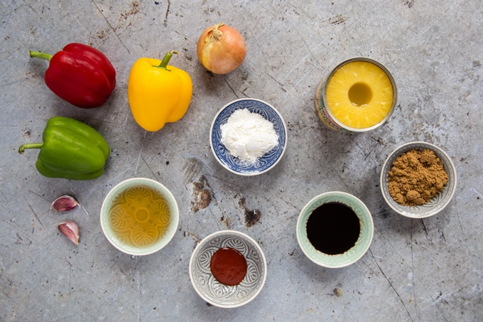 Ingredients for sweet and sour sauce on a rustic, grey work surface. Three whole peppers: red, yellow and green are next to two cloves of garlic and an onion. A tin of pineapple has had its lid removed. Bowls of cornstarch, brown sugaar, dark brown soy sauce, white wine vinegar and red chili sauce are also seen.
