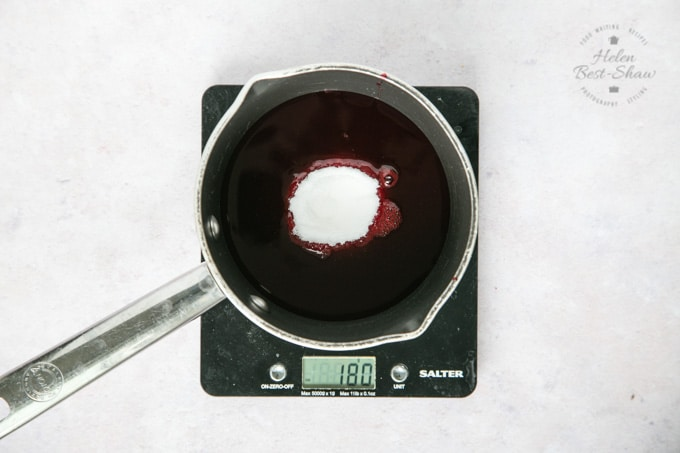 A top down view of a saucepan of blackberry juice. Sugar has just been added, and is visible in the middle of the juice.