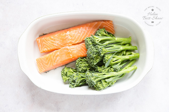 Raw salmon and uncooked tenderstem in a oval porcelain dish, ready to be cooked.
