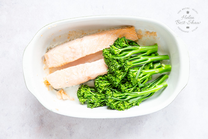 A top down view of a rounded end rectangular dish of cooked salmon and tenderstem in a porcelain dish.