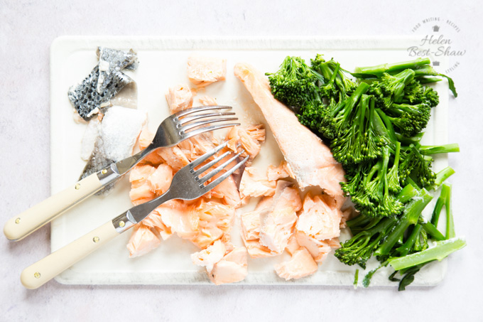 Cooked salmon being deskinned and flaked with two forks. Also on the same chopping board is cooked tenderstem broccoli.