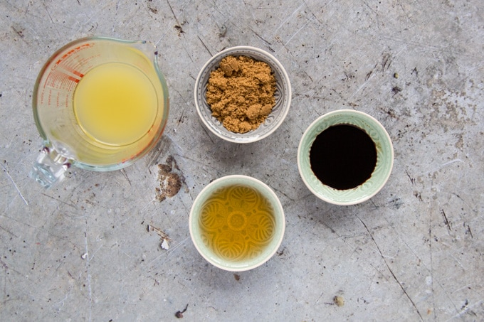 Sauce ingredients for sweet and sour sauce: pineapple juice in a glass jut, and three small bowls containing brown sugar, soy sauce and white wine vinegar. It's a top down picture onto a rustic, grey stone worksurface.