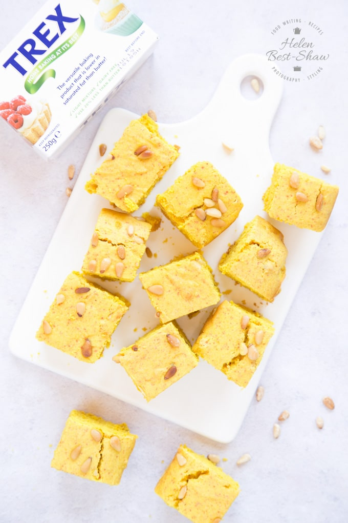 A top down view of squares of yellow sfoof turmeric cake on a square white porcelain board. Next to the board is a packet of vegetable shortening.