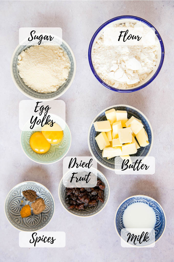 A shot of the ingredients for soul cakes: flour, sugar, butter, milk, raisins, egg yolks and spices, all arranged in seven small dishes laid out on a grey worksurface.