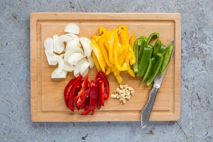 Sliced onion, garlic and yellow, green and red peppers on a wooden board with a kitchen knife. The board is on a grey, rustic stone worksurface.
