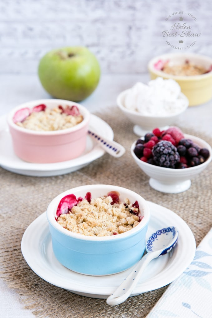 A photograph of wo individual pots of apple and mixed berry crumble, each placed on a sideplate. The plates are on a rustic hessian cloth. China spoons are also resting on the sideplates, and small dishes of frozen berries and coconut yoghurt are to the right of the picture.