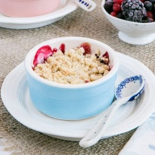 An indivial blue ramekin dish of vegan berry and apple crumble.