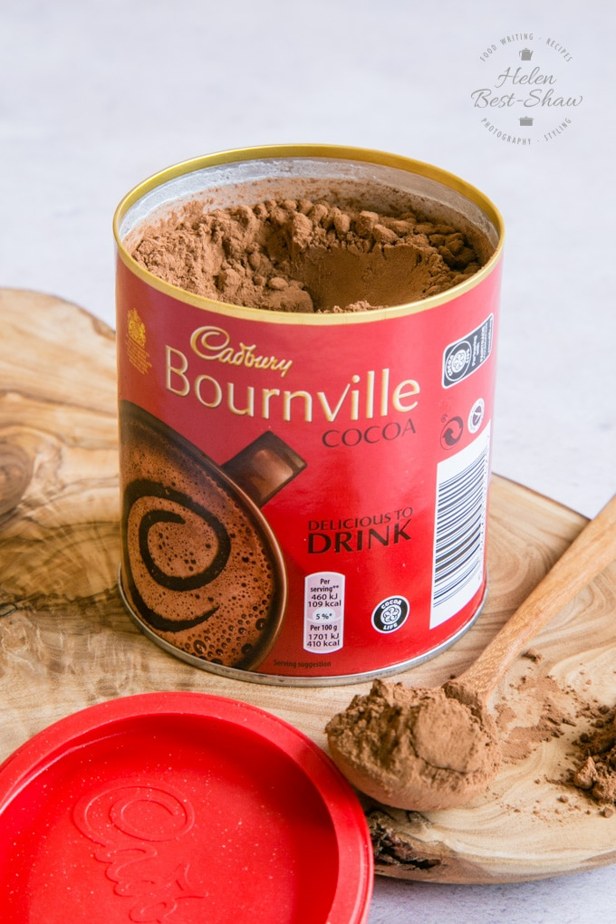 An open tube of Cadbury Bournville cocoa powder on a wooden board. Next to the tube is a small wooden spoon holding powder.