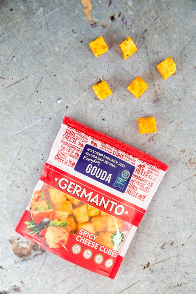 A top down view of a packet of Germanto spicy cheese cubes made from Gouda. Some cubes are sitting on the rustic grey worktop.