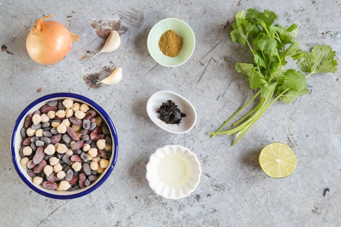 The ingredients for Mexican refried beans laid out on a rustic grey worktop.