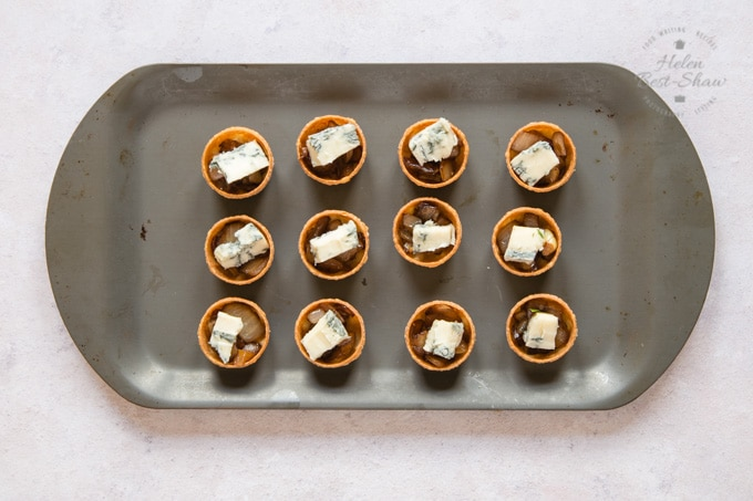A baking tray holding 12 Parma ham, sticky balsamic onion and gorgonzola canapes, ready to go in the oven.
