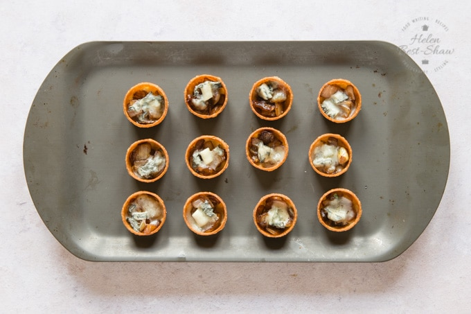 A baking tray holding 12 Parma ham, sticky balsamic onion and gorgonzola canape, just out of the oven.