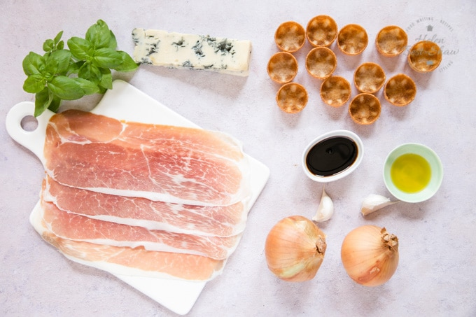 A top down view of slices of Parma ham, gorgonzola cheese, canape cases, balsamic vinegar, oil, garlic and onion, the ingredients for Parma ham canapes with sticky balsamic onion and gorgonzola.