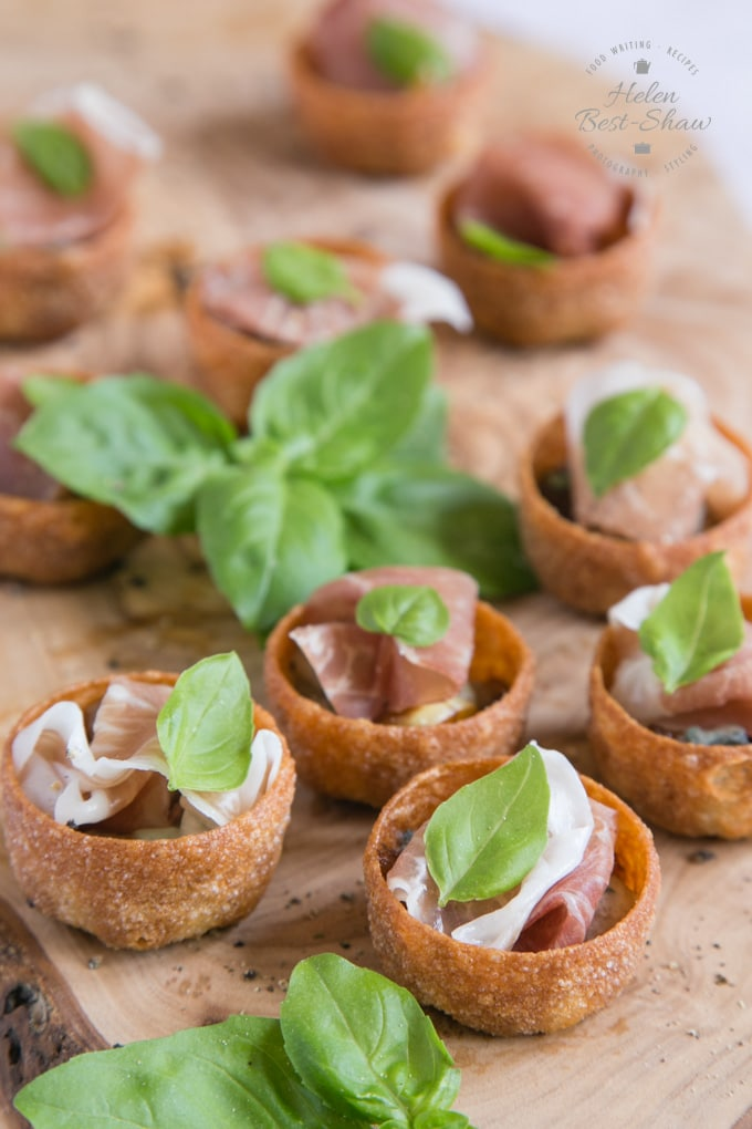 Ten Parma ham canapes with sticky balsamic dressing, onion,and gorgonzola on a wooden board.