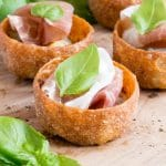 A close up of Parma ham canapes with sticky balsamic onion and gorgonzola cheese.