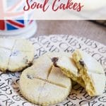 A picture of a sideplate holding four soul cakes: golden biscuits with crosses cut into the top. One has been broken in two, and you can see raisins in the middle. Out of focus towards the back of the picture is a small Union Jack mug.