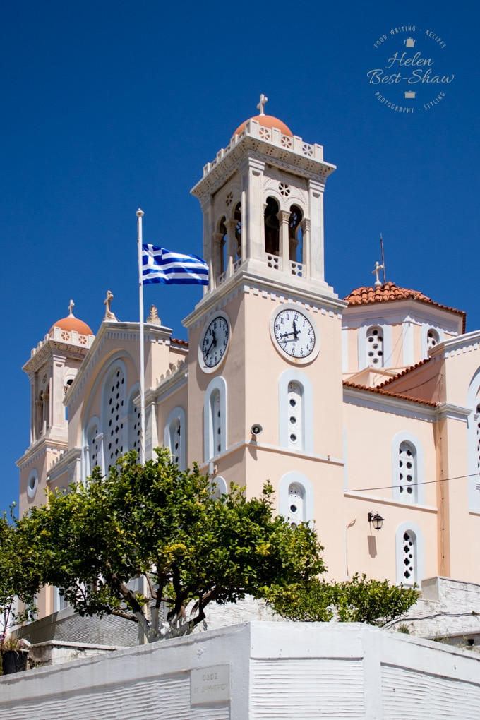 Main church in the villageof Pygros. Painted a pale pink colour wtih a Greek flag flying outside.