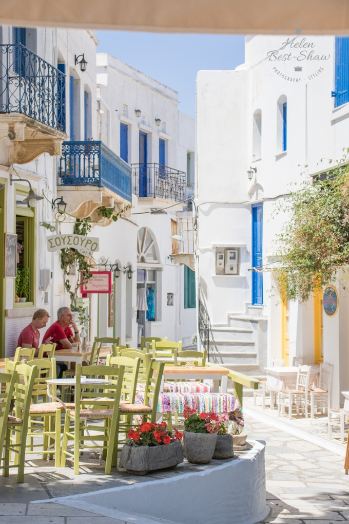 A street scene in Pygros Village, Tinos, Greece. Yellow painted chairs sit outside a cafe against white washed buildings with blue doors and windows.