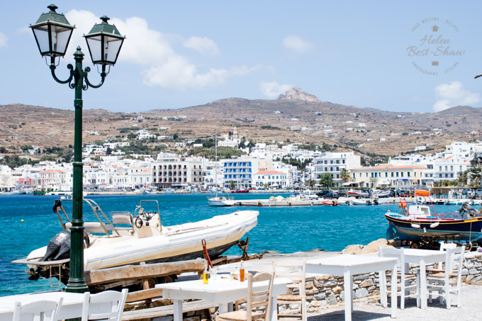 The harbour front of Tinos Town, with a parade of white buildings and bright blue sea