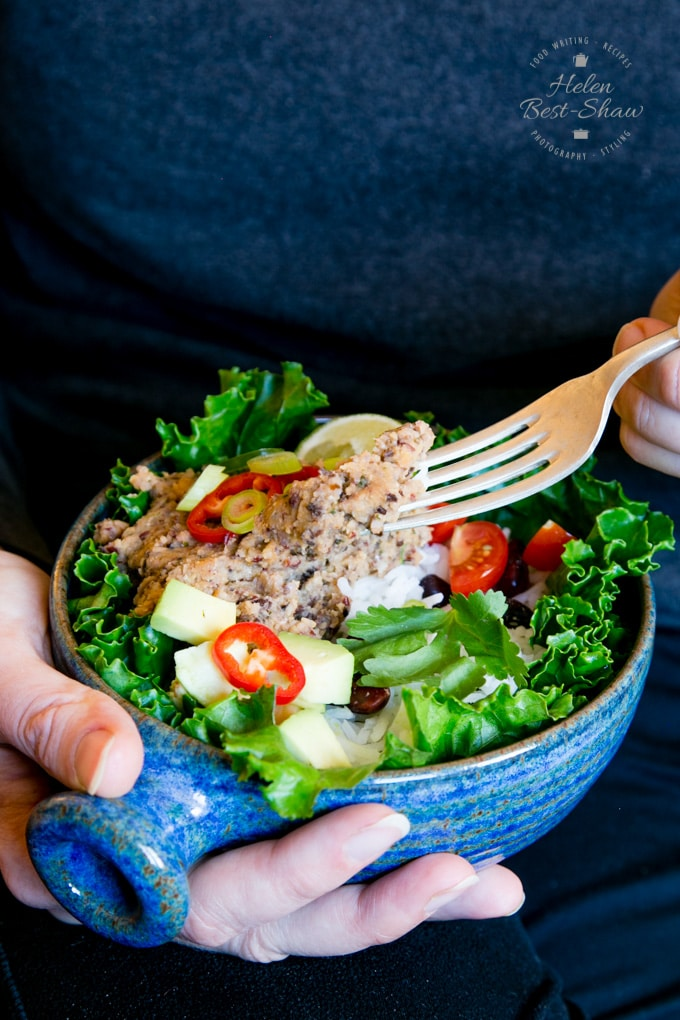 A close-up on a hand-held vegan burrito bowl, with leafy greens, sliced jalapeno peppers and refried beans. The bowl is held in the right hand, and the left hand is holding a forkful of refried beans.