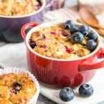 A close up of a an individual casserole dish full of breakfast protein baked oats, garnished with blueberies.