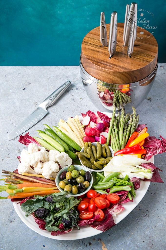 A picture looking down onto a large oval platter of raw vegetable crudités. Behind the platter is the Cuisinepro Egg knife block, holding five knives. One knife is on the mottled grey worktop.