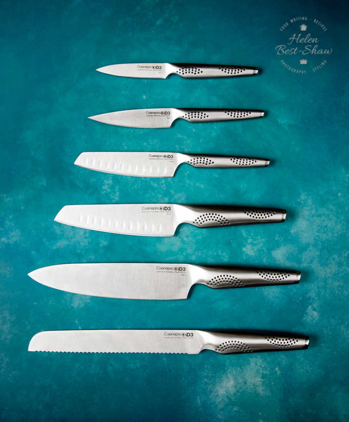 A top to bottom picture of six Cuisinepro kitchen knives arranged smallest to largest on a mottled blue background.
