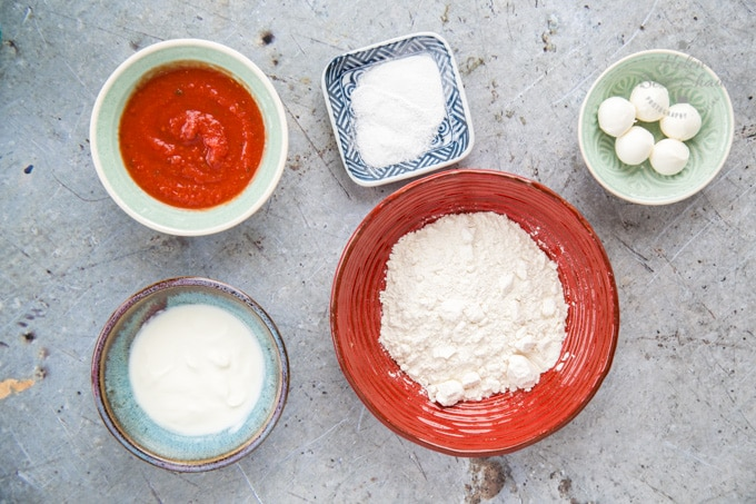 A top down view of the ingredients for emergency no yeast pizza. Separate bowls hold flour, salt and baking powder, yoghurt, tomato sauce and mini mozzarella balls.
