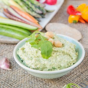 A close up of a small dish of light green coloured goat's cheese and rocket hummus. In the background are some vegetable crudités.