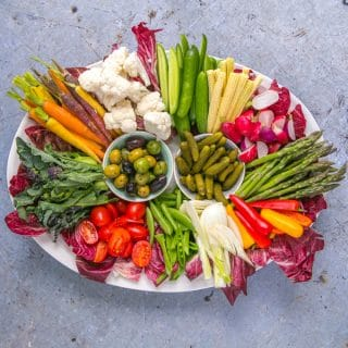 A top down view of an oval platter coverent in vibrantly coloured raw vegetable crudités
