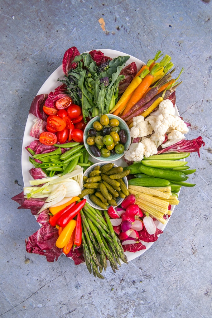 A top down view of an oval platter of raw vegetable crudités of all colours.