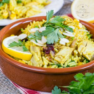 Leftover roast turkey biryani. A close up of the dish arranged in a brown flat bowl, garnished with coriander, almond slivers and a half slice of lemon.