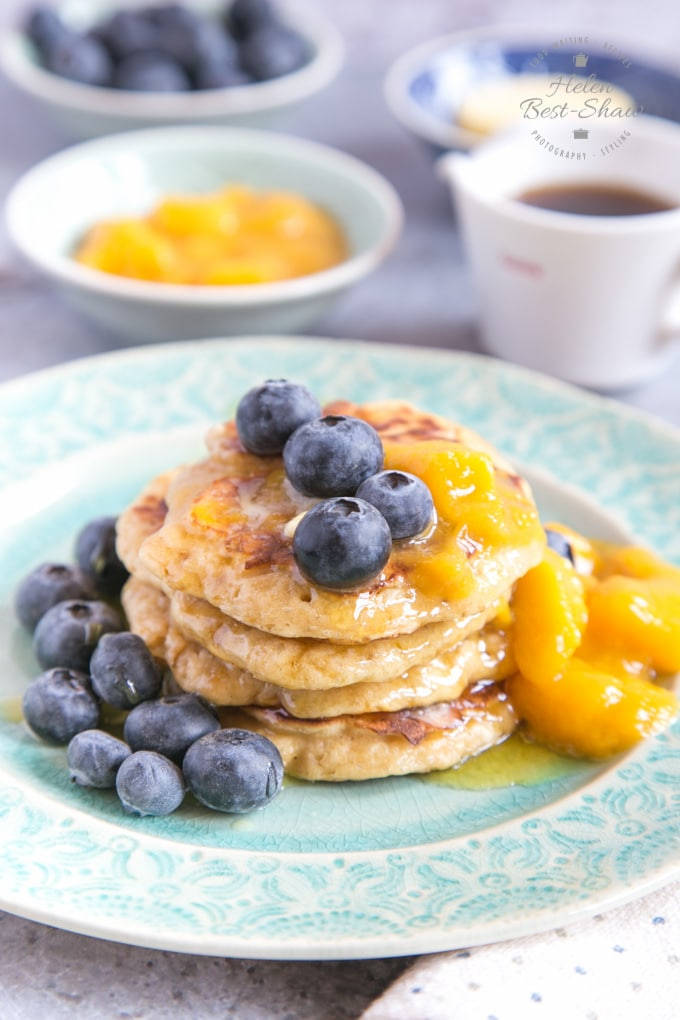 A picture of mango pancakes on a green plate, garnished with syrup, blueberries and mango puree. In the background are small dishes of butter, mango puree, blueberries and a small jug of maple syrup.